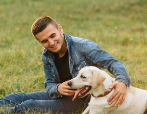 man sitting in grass with dog